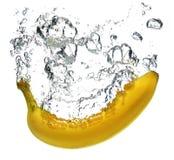 Banane, die in Wasser spritzt Stockfotografie