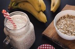 Banane et smoothie sains d'avoine sur le fond noir Image libre de droits