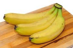 Banane gialle fresche su un bordo di legno per tagliare Fotografia Stock