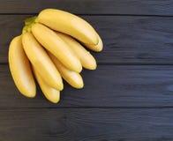 Banane mature sul nero di legno Fotografia Stock Libera da Diritti