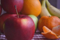 Banane, mele, limone, arancio sulla tavola immagini stock libere da diritti