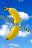 Banane mit Maßband auf Himmelhintergrund Lizenzfreie Stockbilder