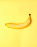 Banane mit messendem Band auf einem gelben Hintergrund Stockbilder