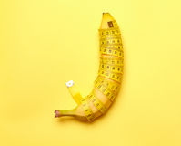Banane mit messendem Band auf einem gelben Hintergrund Lizenzfreie Stockbilder