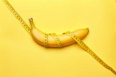 Banane mit messendem Band auf einem gelben Hintergrund Stockbild