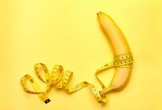 Banane mit messendem Band auf einem gelben Hintergrund Stockfoto