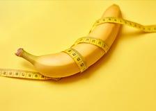 Banane mit messendem Band auf einem gelben Hintergrund Lizenzfreie Stockfotos