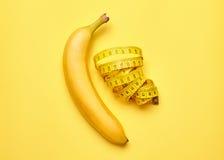 Banane mit messendem Band auf einem gelben Hintergrund Lizenzfreies Stockfoto