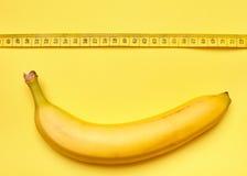 Banane mit messendem Band auf einem gelben Hintergrund Stockfotografie