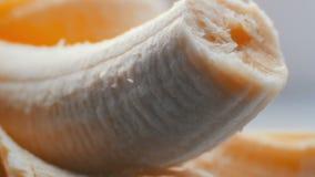 Banane mordue de corps avec la peau sur une fin blanche de macro de fond vers le haut de vue clips vidéos