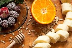 Banane, Orange, gefrorene Erdbeerbrombeeren und Samen klare Smoothiebestandteile auf dem Hintergrund Stockfoto