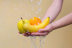 Banane, Orange und Apfel, der in den Händen in den Wassertröpfchen liegt lizenzfreie stockfotos