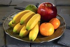 Banane, pomme et mandarine sur une plaque de métal, sur une pierre noire d'ardoise image libre de droits