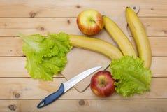 Banane, pommes et leavaes de salade avec le couteau et le plat en bois de coupe sur un fond en bois Photos stock