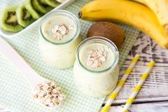 Banane Smoothie mit Kiwi und Hafern auf einem hellen Holztisch Lizenzfreie Stockfotos