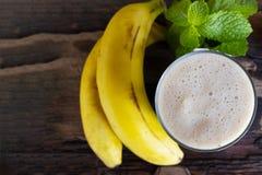 Banane Smoothies Saft und Banane tragen für Milchshaken auf hölzernem Hintergrund von der Draufsicht Früchte lizenzfreie stockfotos