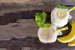 Banane Smoothiessaft und gelbes Bananenfruchtgetränk gesund der Geschmack lecker im Glas für für Milchshaken auf hölzernem Hinter stockfotografie