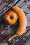Banane und Apfel auf der alten Tabelle Lizenzfreie Stockfotografie