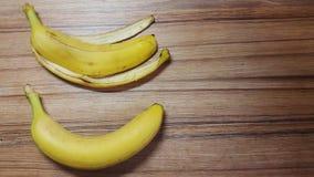 Banane und Bananenschale auf einem Holztisch Stockbilder