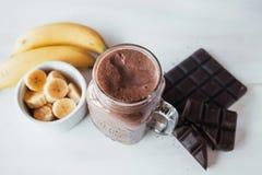 Banane und Schokolade Smoothie im Glasgefäßmilchshake-, natürlichen und organischengetränk lizenzfreie stockfotos