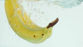 Bananen, die in Wasser auf weißem Hintergrund in der Zeitlupe tauchen lizenzfreie stockbilder