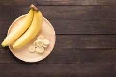 Bananen in einem hölzernen Teller auf einem hölzernen Hintergrund Raum für Text Stockfotos