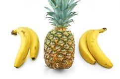 Bananen en ananas op wit worden geïsoleerd dat stock foto's