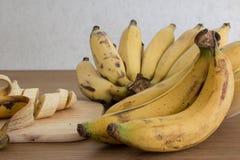 Bananen en een gesneden banaan, close-up, diepte van gebied Royalty-vrije Stock Foto
