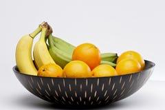 Bananen en sinaasappelen in een zwarte komclose-up Royalty-vrije Stock Afbeelding