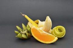 Bananen, kiwin, apelsinen och äpplet skalar på en svart bakgrund arkivfoto