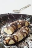 Bananen mit Schokolade und Puderzucker Stockfoto