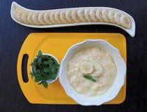 Bananen-Pudding in einer gelben Schüssel für Eiscreme mit geschnittener †‹â€ ‹Banane und Minze Stockbilder