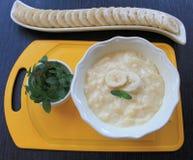 Bananen-Pudding in einer gelben Schüssel für Eiscreme mit geschnittener †‹â€ ‹Banane und Minze Lizenzfreie Stockbilder