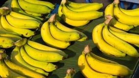 Bananen säljs av grupper i marknad Arkivfoton