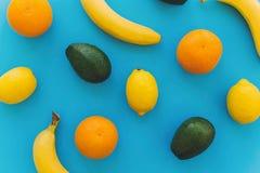 Bananen, sinaasappelen, citroenen, avocado op blauw in document backgroun Stock Foto's