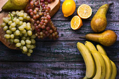 Bananen, Trauben, peares und limons auf dem purpurroten Hintergrund Lizenzfreie Stockfotos