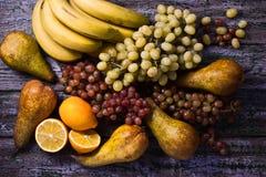 Bananen, Trauben, peares und limons auf dem purpurroten Hintergrund Stockfoto