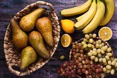 Bananen, Trauben, peares und limons auf dem purpurroten Hintergrund Stockbilder