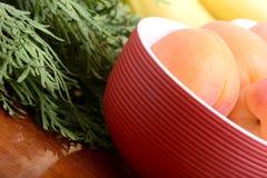 Bananen und Aprikosen auf roter Platte, Abschluss oben stockfotos