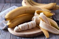 Bananen und Bananenscheiben auf einem hölzernen Brett Lizenzfreies Stockfoto