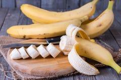 Bananen und Bananenscheiben auf einem hölzernen Brett Lizenzfreies Stockbild