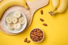 Bananen und Bananenscheiben auf einer Platte des Holzes Lizenzfreie Stockbilder
