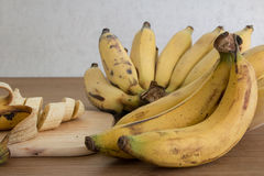 Bananen und eine geschnittene Banane, Nahaufnahme, Schärfentiefe Lizenzfreies Stockfoto