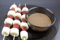 Bananen und Erdbeeren auf einem hölzernen Stock nahe bei einer Schüssel geschmolzener Schokolade lizenzfreie stockfotografie