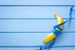Bananen und messende Linien legten auf blauen Bretterboden - belasten Sie L Lizenzfreie Stockfotografie