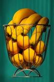 Bananen und Orangen im Eisenkorb mit aquamarinem Vorhang als Hintergrundschwimmen Stockfotos