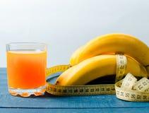 Bananen und Orangensaft auf einem hölzernen Hintergrund Lebensmittel für Gewicht lizenzfreie stockfotos