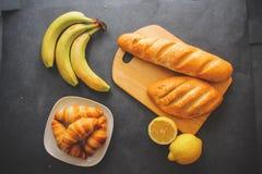 Bananen, Zitronen, man schnitten, Laibe des Weißbrots auf dem Brett und vier Hörnchen auf einer silbernen Servierplatte auf einem lizenzfreies stockfoto