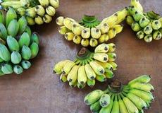 Bananenbündel roh und reif auf Holztisch Stockfotografie