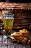 Bananenkleiner kuchen auf einem hölzernen Stand Transparentes Cup mit grünem Tee Lizenzfreies Stockbild